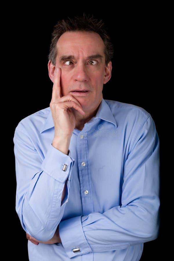 Uomo di affari di medio evo che tira fronte Eyed incrocio divertente fotografia stock libera da diritti