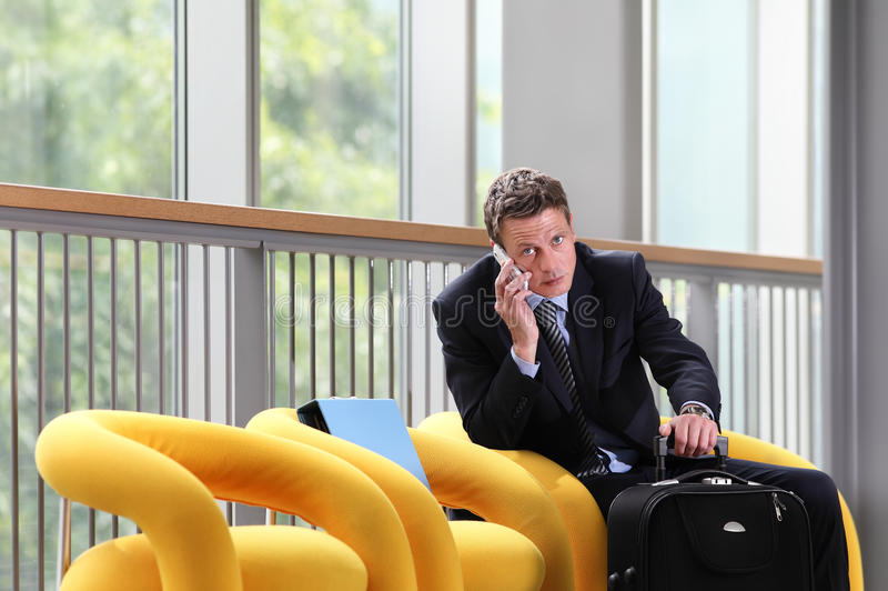 Uomo di affari di viaggio che parla sul telefono, sedentesi con i bagagli, sala di attesa, sedia gialla immagine stock