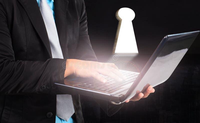 Uomo di affari e computer portatile e luce del computer da uso del foro chiave per fotografie stock libere da diritti