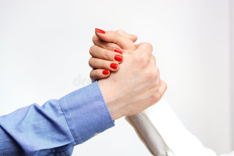 Uomo di affari e donna di affari che stringe le mani che suggeriscono uguaglianza di genere all'ufficio immagini stock