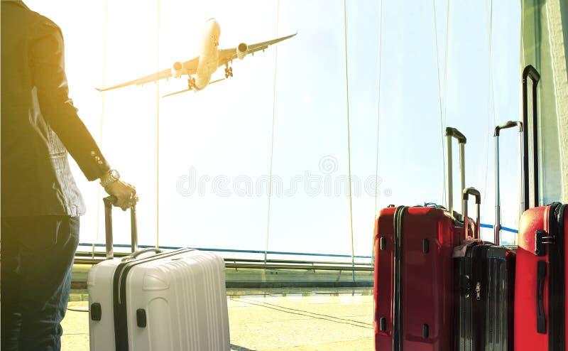 Uomo di affari e pila di bagagli di viaggio che stanno nell'aeroporto fotografie stock
