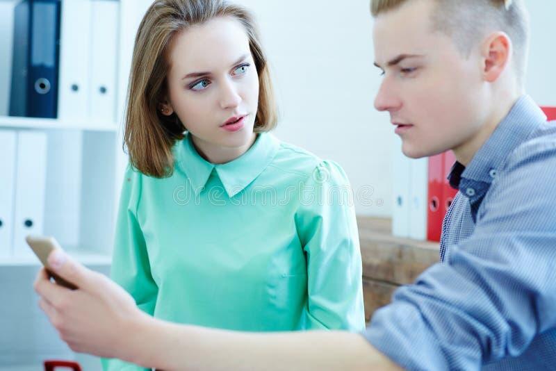 Uomo di affari e signora di affari che guarda qualcosa sullo schermo dello smartphone Giovani soci commerciali che discutono le i fotografia stock libera da diritti
