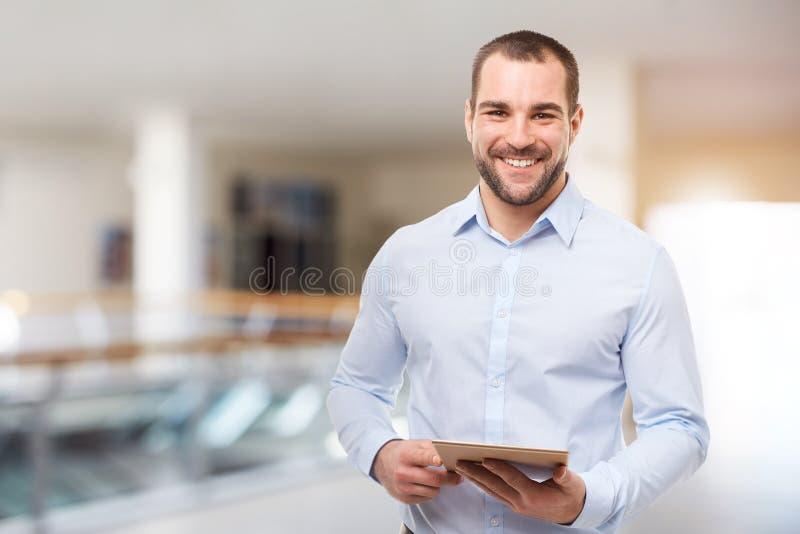 Uomo di affari nel centro di affari con il computer della compressa fotografia stock libera da diritti
