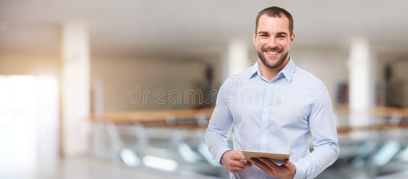 Uomo di affari nel centro di affari con la compressa immagine stock