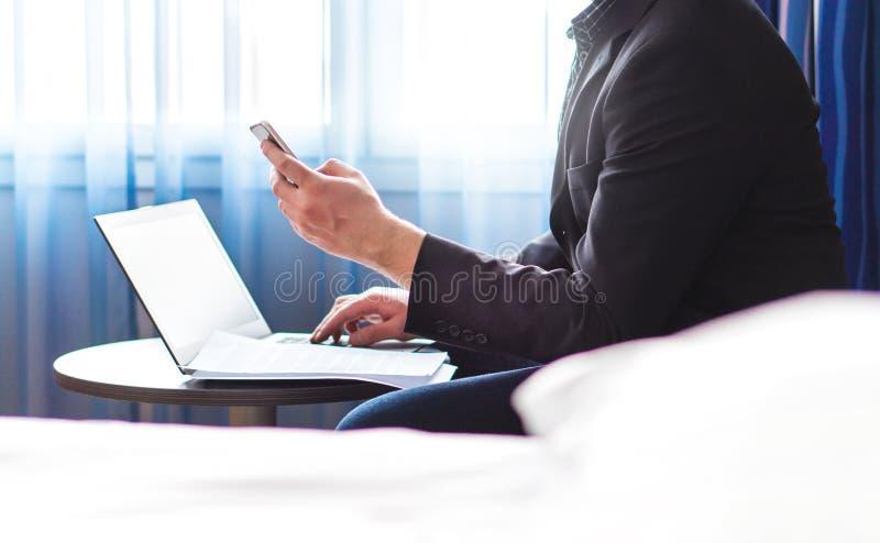 Uomo di affari nella camera di albergo con lo smartphone ed il computer portatile fotografie stock libere da diritti
