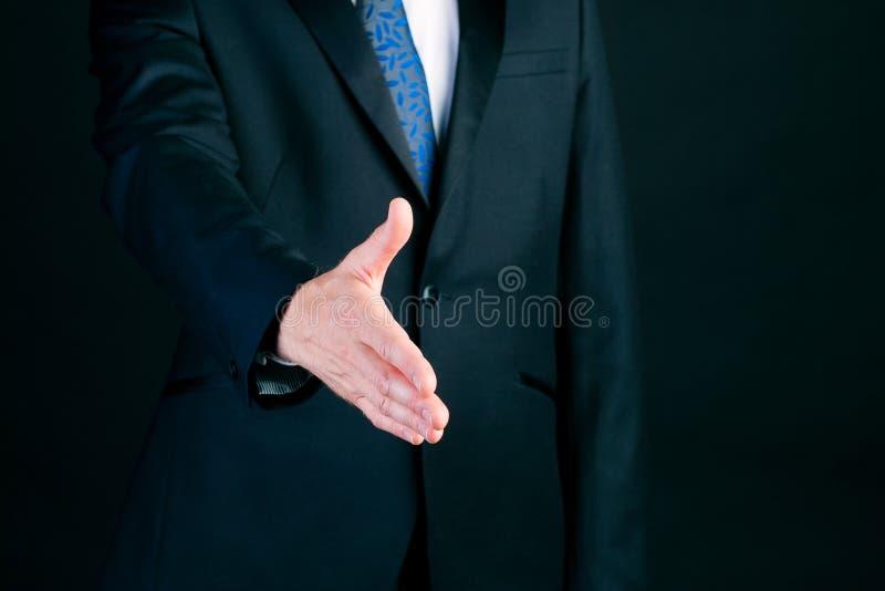Uomo di affari nella stretta di mano d'offerta del vestito fotografia stock libera da diritti