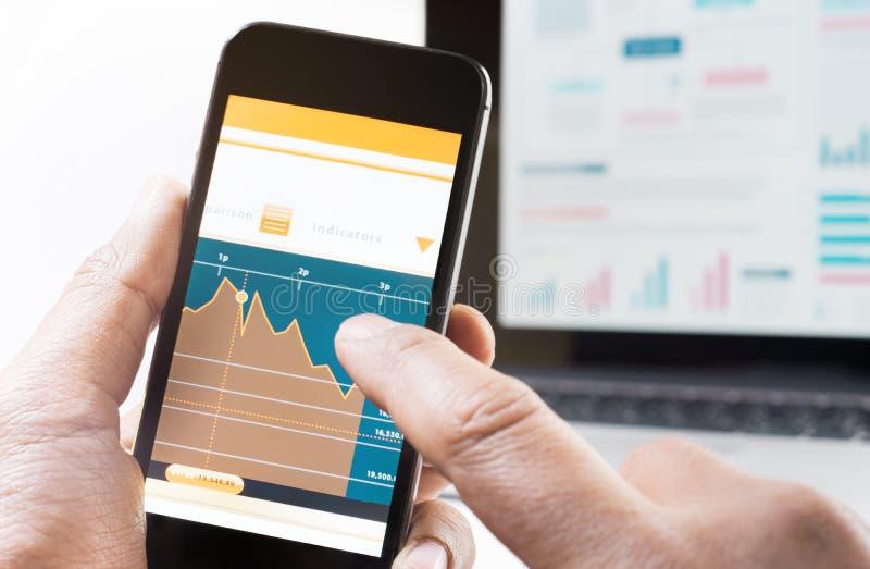 Uomo di affari online che controlla mercato azionario con lo Smart Phone immagini stock libere da diritti