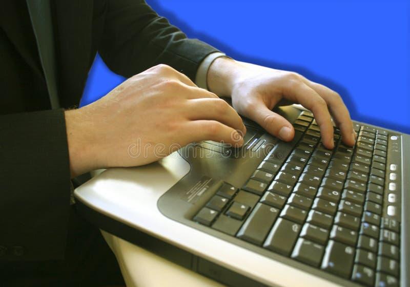 Uomo di affari su un computer portatile fotografia stock libera da diritti