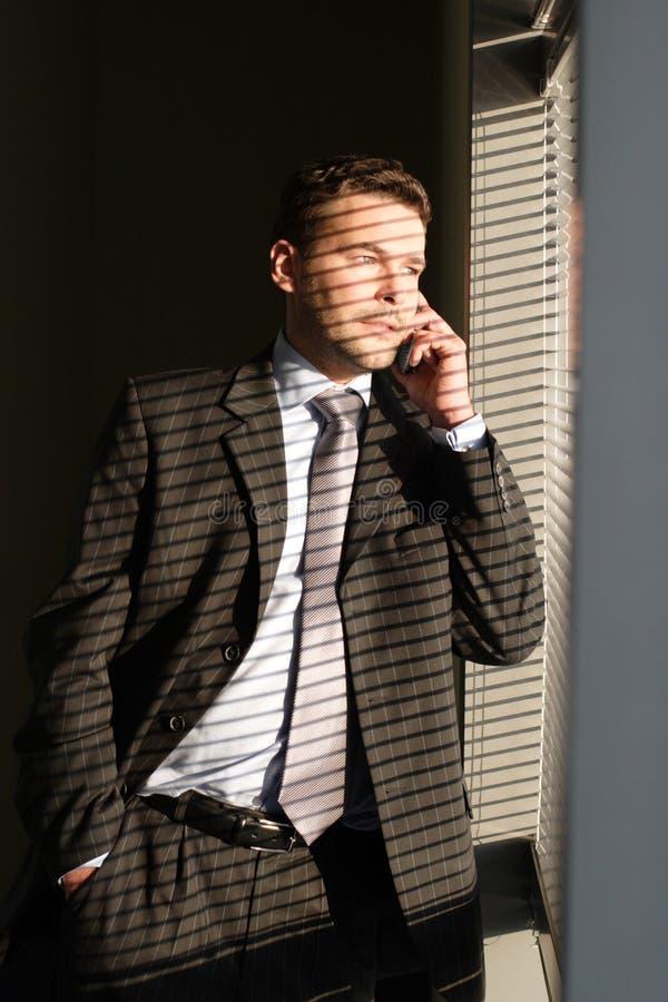 Uomo di affari sul telefono che osserva attraverso i ciechi di finestra fotografie stock