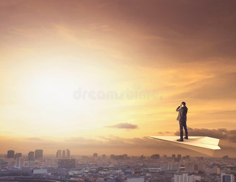 Uomo di affari sull'aereo di carta che spia da binoculare alla scena urbana fotografia stock libera da diritti