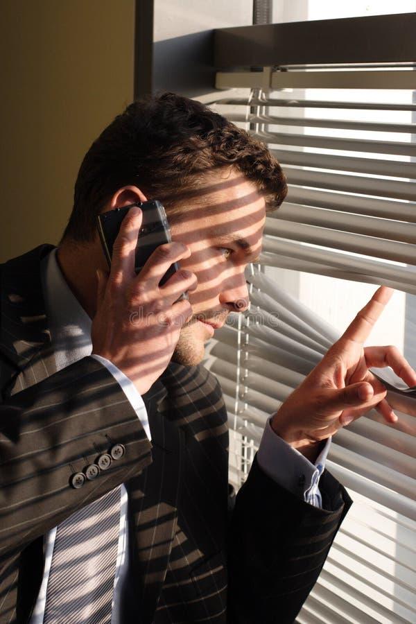 Uomo di affari sullo sguardo del telefono immagine stock
