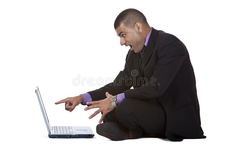 Uomo di affari trovato sorprendente sul suo computer portatile fotografia stock libera da diritti