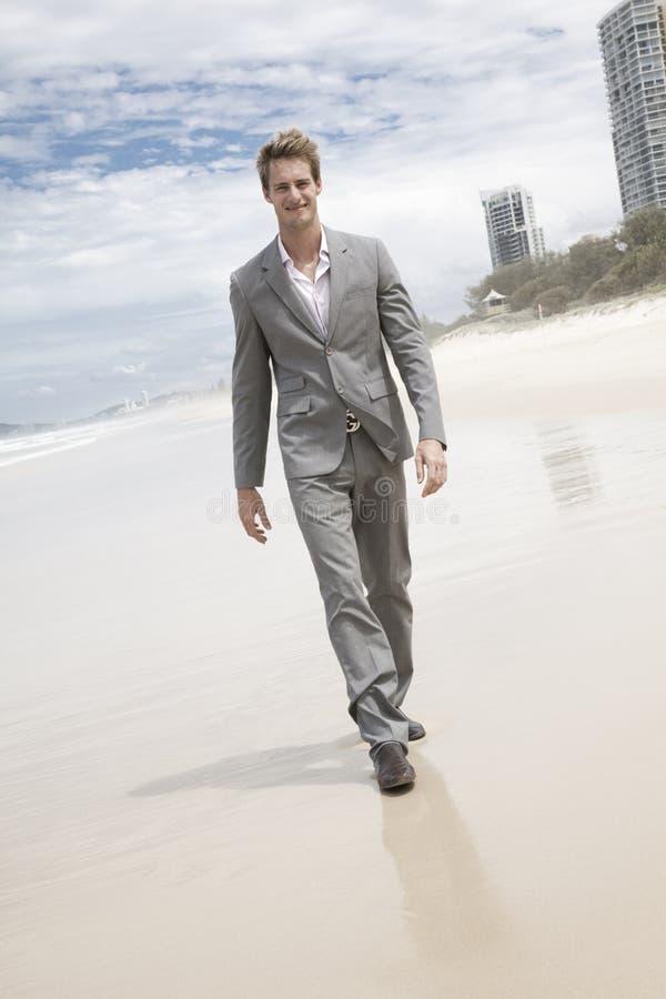 Uomo di affari in vestito che cammina sulla spiaggia immagini stock
