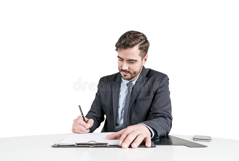 Uomo di affari in vestito che firma un contratto o alcune carte immagini stock