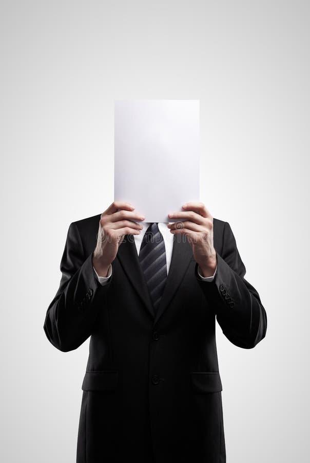 Uomo di affari in vestito scuro che tiene un segno in bianco fotografia stock libera da diritti