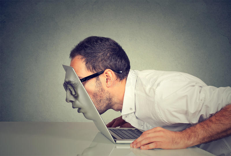Uomo di affari in vetri che passano il suo capo tramite uno schermo del computer portatile fotografia stock