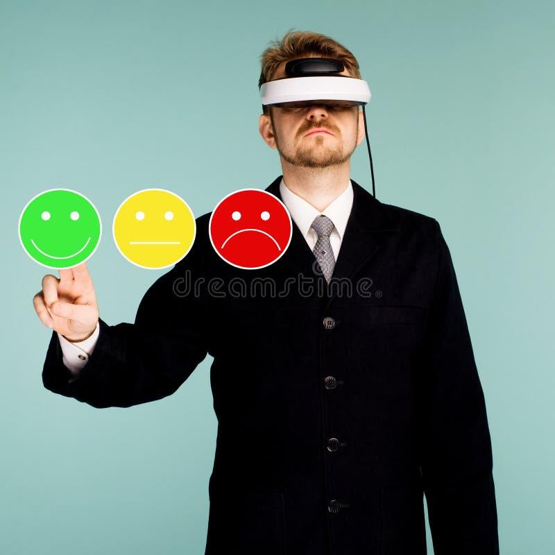 Uomo di affari in vetri virtuali che danno valutazione e rassegna con l'icona sorridente felice dell'emoticon del fronte Soddisfa fotografia stock
