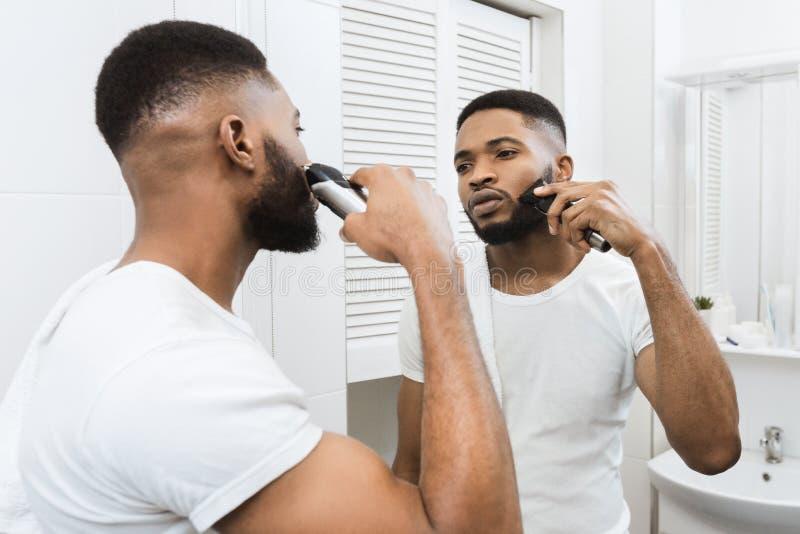 Uomo di afro che rade il suo fronte fotografia stock libera da diritti