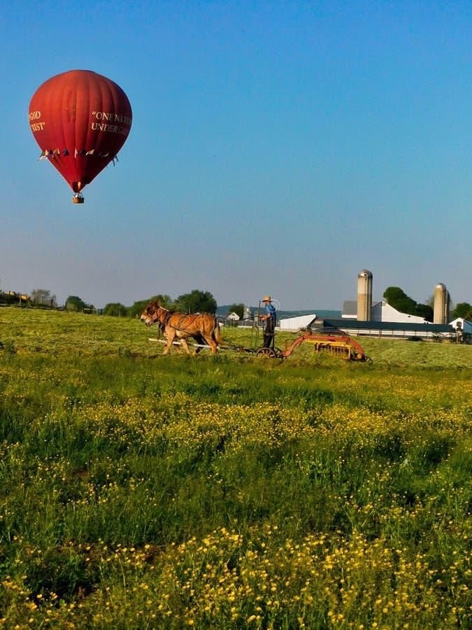 Uomo di Amish che ara un campo, con la mongolfiera che si libra sopra fotografia stock libera da diritti