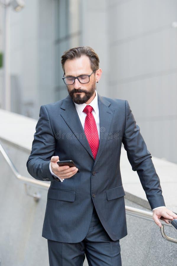 Uomo di calma che esamina lo smartphone mentre leggendo i messaggi immagine stock libera da diritti