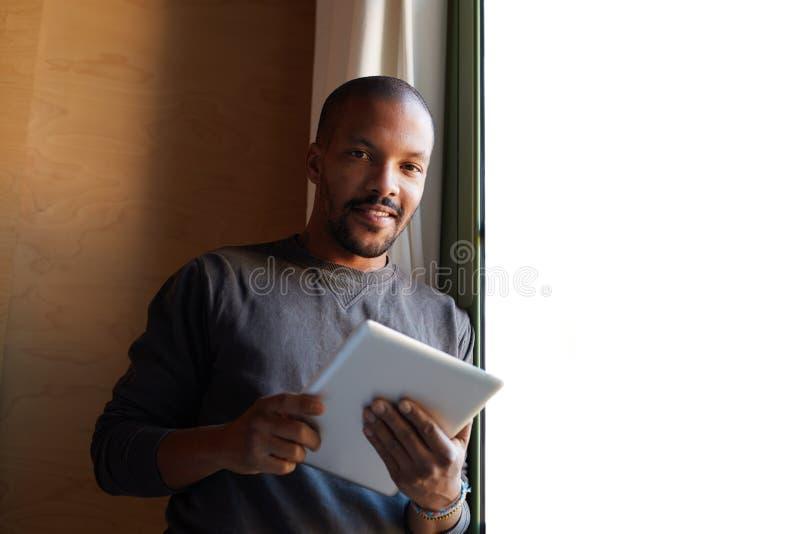 Uomo di colore africano felice che usando il salone della compressa a casa fotografia stock libera da diritti