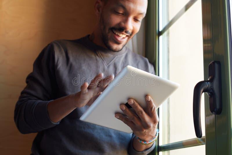 Uomo di colore africano sorridente che usando il salone della compressa a casa fotografia stock