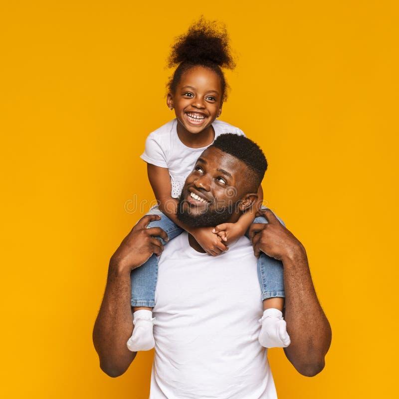 Uomo di colore allegro che guida il suo sveglio poca figlia sulle spalle fotografie stock