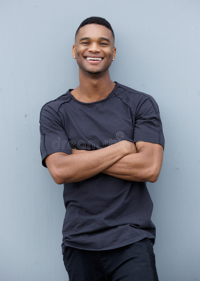 Uomo di colore amichevole che sorride con le armi attraversate fotografia stock libera da diritti