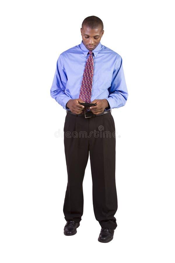 Uomo di colore casuale Texting sul suo telefono delle cellule fotografia stock