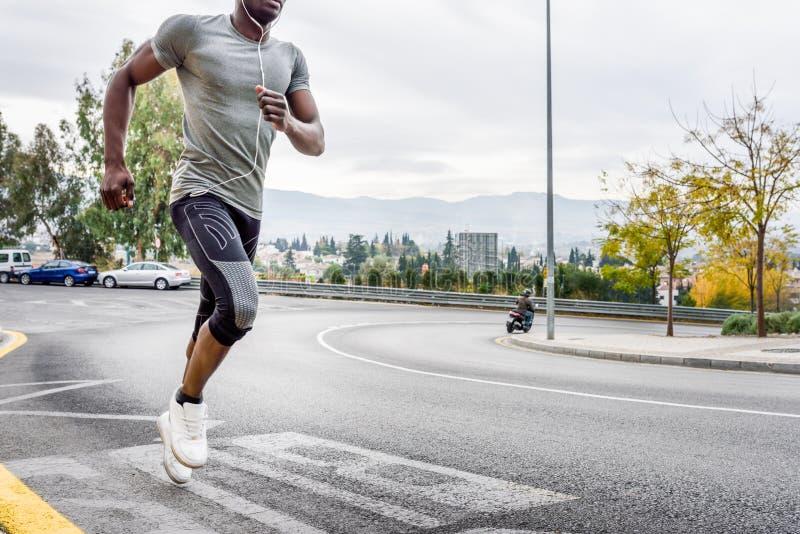 Uomo di colore che corre all'aperto in strada urbana immagine stock libera da diritti