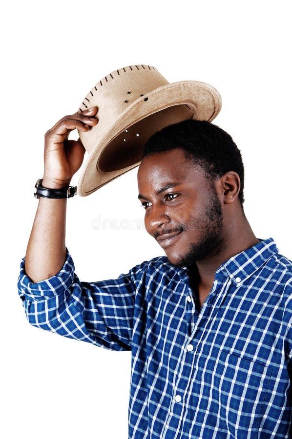Uomo di colore che solleva il suo cappello. immagini stock