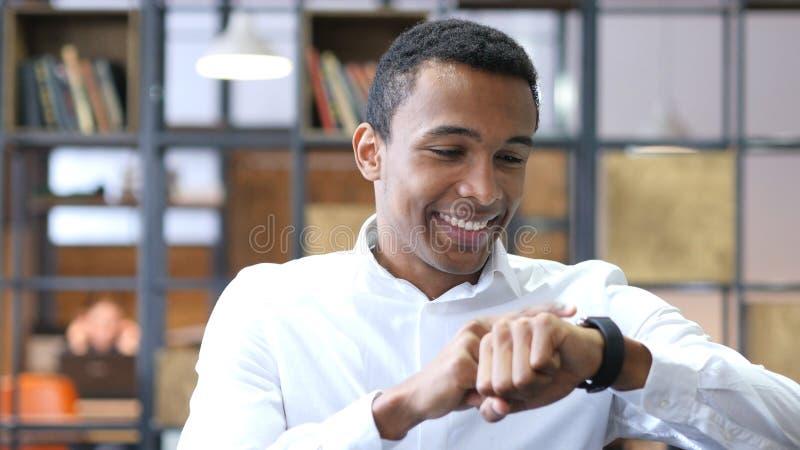 Uomo di colore che utilizza Smartwatch nell'ufficio fotografia stock libera da diritti