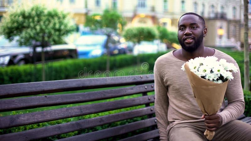 Uomo di colore con i fiori che si siedono sul banco, amica aspettante, anticipazione fotografia stock libera da diritti