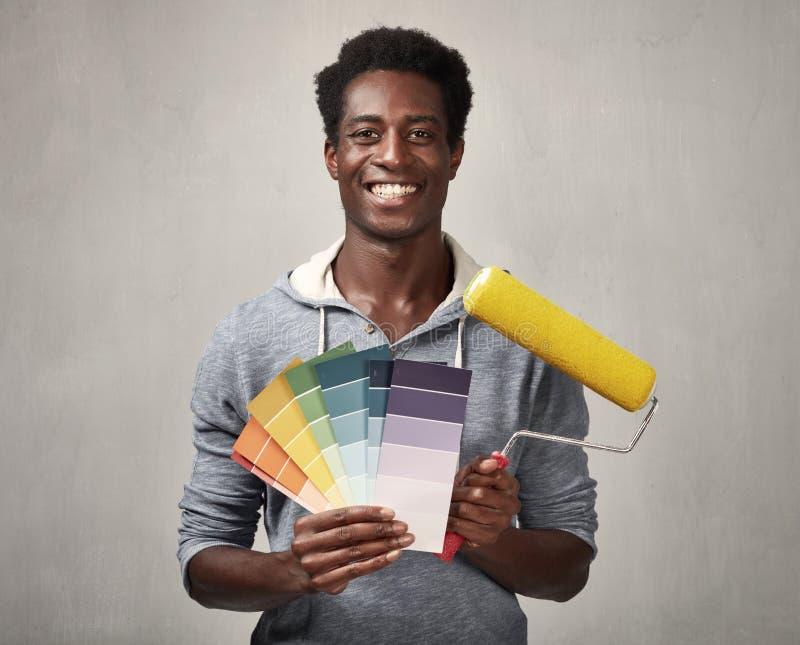 Uomo di colore con il rullo di pittura fotografia stock