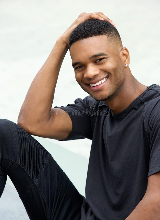 Uomo di colore felice che sorride contro il fondo bianco fotografia stock