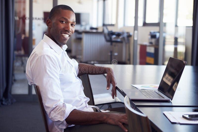 Uomo di colore giovane che si siede allo scrittorio in ufficio che sorride alla macchina fotografica fotografie stock