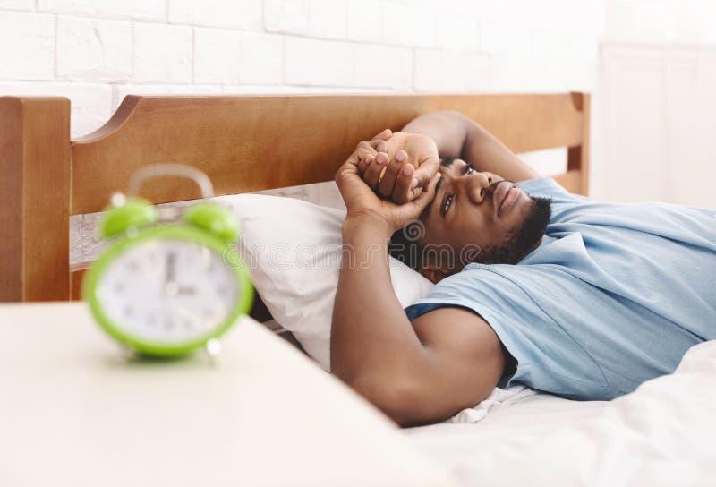 Uomo di colore a letto che soffre dall'insonnia e dai disturbi del sonno immagini stock libere da diritti
