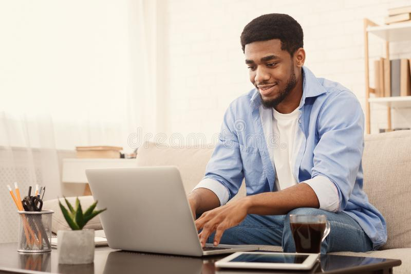 Uomo di colore millenario che lavora al computer portatile in Ministero degli Interni immagine stock libera da diritti