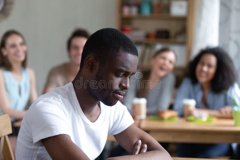 Uomo di colore turbato che si siede da solo i compagni di scuola che lo scherniscono immagine stock