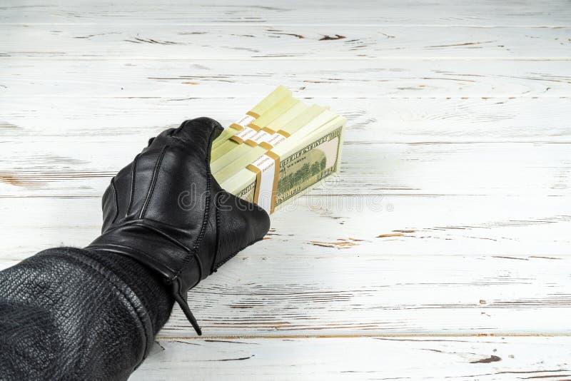 Uomo di concetto di crimine in guanti di cuoio neri che tengono i mattoni di soldi immagini stock