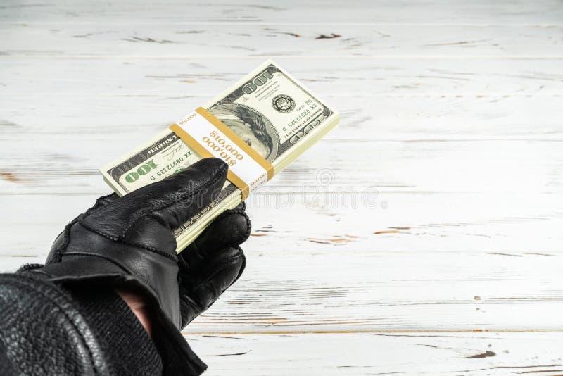 Uomo di concetto di crimine in guanti di cuoio neri che tengono i mattoni di soldi fotografie stock libere da diritti