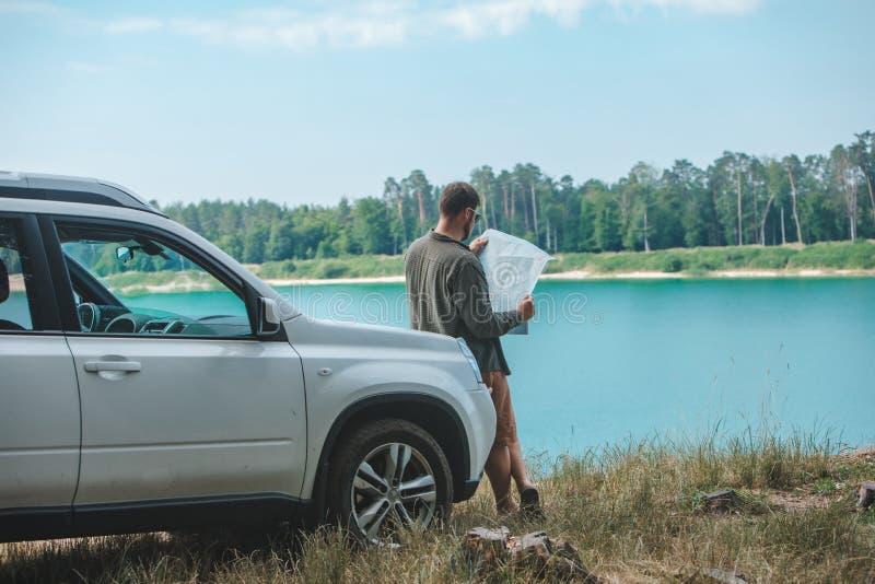 Uomo di concetto di viaggio di automobile che considera l'uomo nel lago del cappuccio dell'automobile del suv su fondo fotografie stock libere da diritti