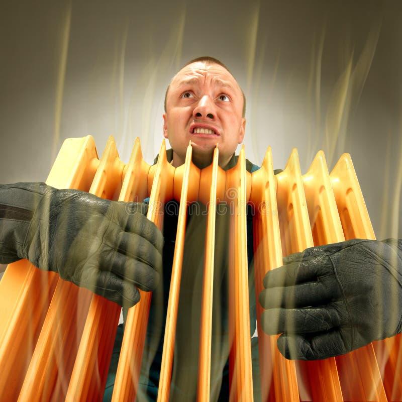 Uomo di congelamento che tiene il radiatore dell'olio caldo fotografie stock