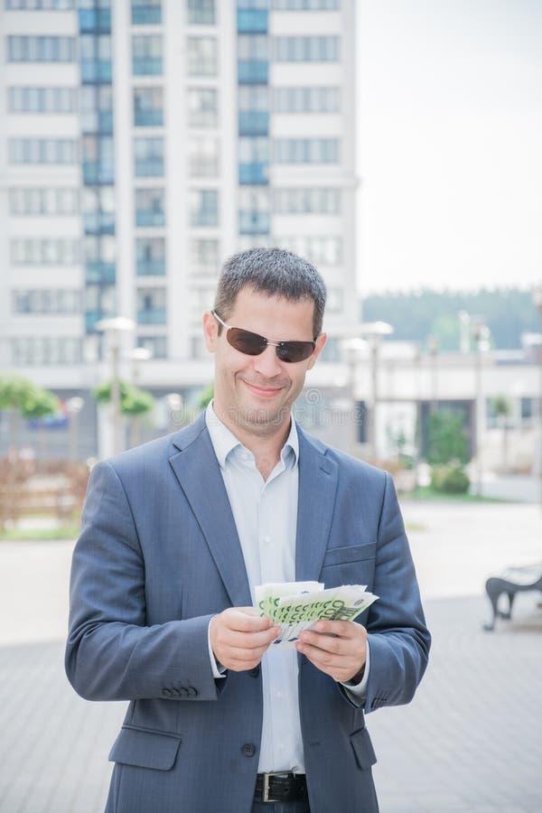 Uomo di conquista felice di affari che tiene i suoi pollici su con le euro fatture di soldi immagini stock libere da diritti