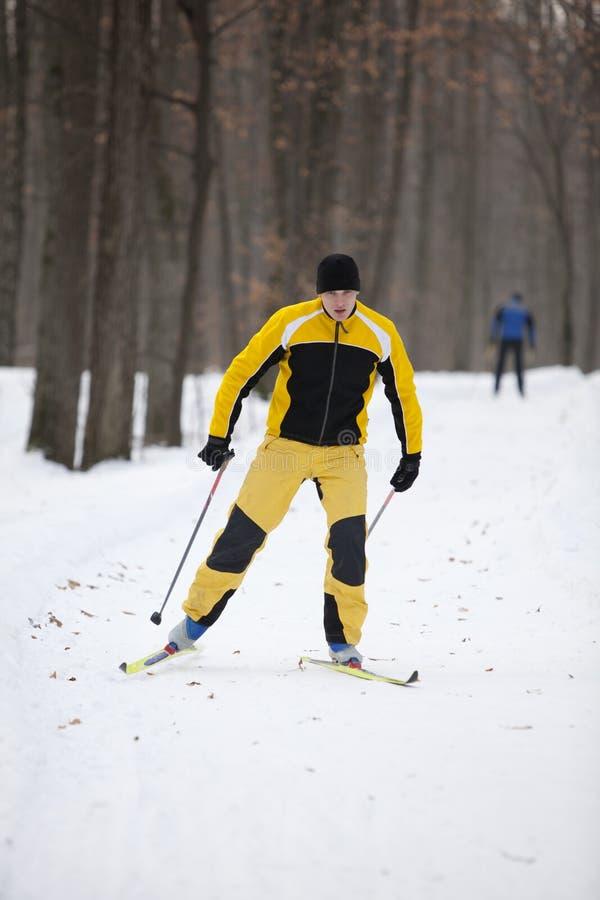 Uomo di corsa con gli sci che attraversa il paese immagini stock