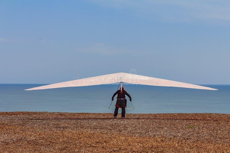 Uomo di deltaplano su un'ala bianca che salta giù una scogliera al divertimento forte immagini stock libere da diritti