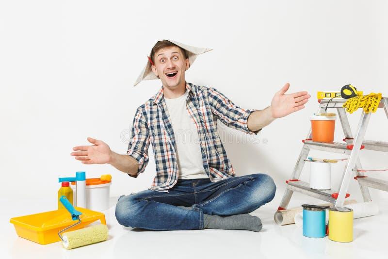 Uomo di divertimento in cappello del giornale con la matita dietro l'orecchio che si siede sul pavimento con gli strumenti per l' immagini stock