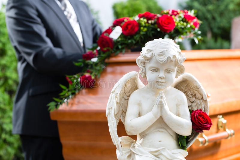 Uomo di dolore al funerale con la bara immagine stock