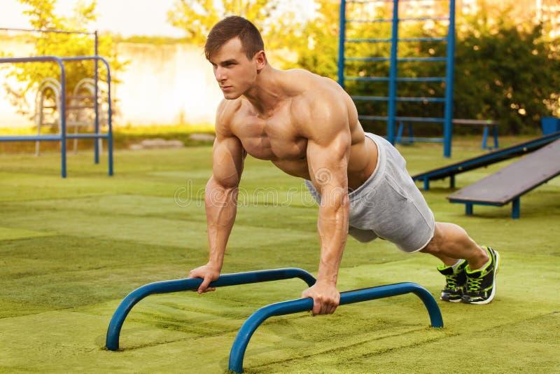 Uomo di forma fisica che fa spinta-UPS nello stadio, allenamento di addestramento trasversale Addestramento maschio sportivo fuor fotografie stock libere da diritti