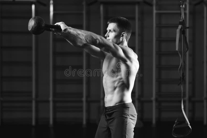 Uomo di forma fisica che fa un addestramento del peso mediante il sollevamento del kettlebell immagine stock